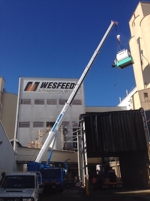 Mobile Crane Lifting Machinery into Wesfeeds Building